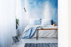 Coperta e libri modellati sulla tavola nei wi interni della camera da letto blu Fotografia Stock Libera da Diritti