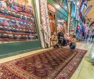 Coperte e tappeti di acquisto dei turisti nel grande bazar immagine stock