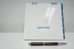 Copertina alta falsa isolata della copertura del calendario con la penna Fotografie Stock Libere da Diritti