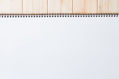 Copertura bianca in bianco vuota della pagina anteriore del blocco note diretto a spirale sui precedenti di legno Immagini Stock Libere da Diritti
