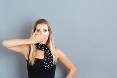 Copertura della giovane donna la sua bocca Immagine Stock