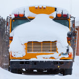 Copertura di neve parcheggiata della bufera di neve di inverno dello scuolabus Immagine Stock