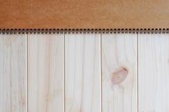 Copertura marrone in bianco vuota della pagina anteriore del blocco note diretto a spirale sui precedenti di legno Immagine Stock Libera da Diritti