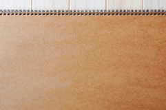 Copertura marrone in bianco vuota della pagina anteriore del blocco note diretto a spirale sui precedenti di legno Immagini Stock Libere da Diritti