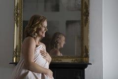 Copertura sorridente lei stessa della donna con la trapunta Fotografie Stock