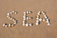 Coperture del mare di parola scritte sulla sabbia della spiaggia Immagine Stock