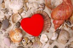 Coperture del mare e cuore rosso fotografia stock