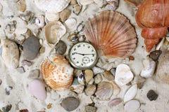 Coperture del mare ed orologio dell'annata sulla sabbia Immagini Stock