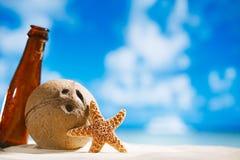 Coperture delle stelle marine e della noce di cocco con il sole, l'oceano, la spiaggia e la vista sul mare Fotografia Stock