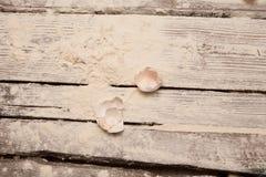 Coperture delle uova su una tavola di legno con farina fotografia stock libera da diritti