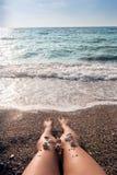 Coperture sui piedi del ` s della donna alla riva di mare Immagine Stock Libera da Diritti