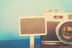 Copi il contrassegno dello spazio e la macchina fotografica di legno dell'annata sulla tavola di legno con fondo blu Fotografia Stock