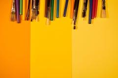 Copi lo spazio con le spazzole e le penne multicoloured su giallo Immagine Stock