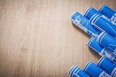 Copi lo spazio dei disegni di ingegneria rotolati blu sul bordo di legno c Immagine Stock Libera da Diritti