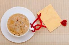 Copia-spazio caldo della carta in bianco di amore di simbolo del cuore della bevanda del caffè bianco della tazza Fotografia Stock