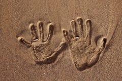 Copie de main d'amour avec des anneaux de mariage sur le sable Image libre de droits