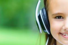 Copie el espacio y la media cara de la música que escucha de la muchacha caucásica atractiva joven con los auriculares profesiona Fotografía de archivo libre de regalías