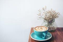 Copie la imagen del espacio de una taza azul de café caliente del latte y de flores secas en un florero en la tabla de madera del Imagenes de archivo