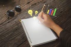 Copie o espaço da mão da mulher que escreve para baixo no caderno branco com ícone da ideia e do gráfico foto de stock royalty free