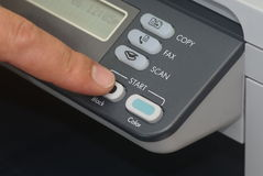 Coping. A finger pushing a start button on copy machine Royalty Free Stock Photography