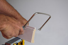 Coping with Saw. Using a coping saw to make smooth joint with hands Royalty Free Stock Image