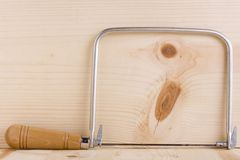 Coping saw. Next to a piece of wood Royalty Free Stock Photo