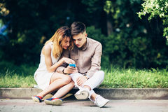 Cople utilisant un smartphone, se reposant en parc Photo libre de droits