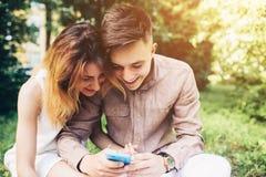 Cople utilisant un smartphone, se reposant en parc Image libre de droits