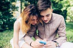 Cople utilisant un smartphone, se reposant en parc Photos libres de droits