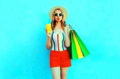Copo à moda da terra arrendada da mulher do suco de fruto com os sacos de compras no t-shirt colorido, chapéu de palha do verã foto de stock