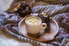 Copo acolhedor do chocolate quente com creme e canela, luzes e cobertura fotos de stock royalty free
