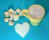 Copo amarelo com cappuccino, coração feito do açúcar e conchas do mar em um fundo azul fotos de stock royalty free