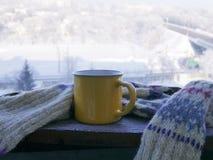 Copo amarelo com o chá quente envolvido com um lenço de lã em uma superfície de madeira contra o contexto de uma paisagem nevado fotos de stock