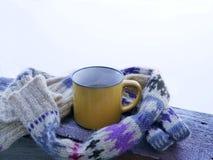 Copo amarelo com o chá quente envolvido com um lenço de lã em uma superfície de madeira contra o contexto de uma paisagem nevado foto de stock