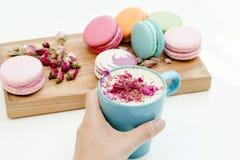 Copo azul do cappuccino da posse da mão da mulher com pétalas de rosas e macarons da beleza na mesa de madeira Imagens de Stock Royalty Free