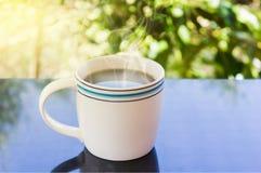 Copo branco clássico do café preto com fundo da árvore Fotografia de Stock