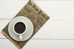 Copo branco com café preto e o jornal velho em um fundo arborizado branco Café em um fundo arborizado branco Vista de acima pl fotos de stock royalty free