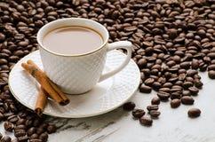 Copo branco com feijões de café e varas de canela Foto de Stock