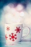 Copo branco com os flocos de neve vermelhos no fundo do bokeh do inverno Imagens de Stock Royalty Free