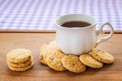 Copo branco da porcelana com chá e as cookies de farinha de aveia doces com partes de chocolate escuro em uma placa de madeira ca imagens de stock