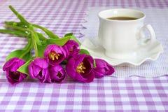 Copo branco da porcelana com chá ou café em pires com borda ondulada e um ramalhete de tulipas roxas em uma toalha de mesa quadri foto de stock royalty free