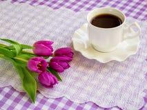 Copo branco da porcelana do chá ou do café em pires com borda ondulada e um ramalhete de tulipas roxas em uma toalha de mesa quad fotos de stock royalty free