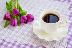 Copo branco da porcelana do ch? ou do caf? em pires com borda ondulada e um ramalhete de tulipas roxas em uma toalha de mesa quad fotografia de stock royalty free