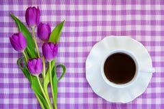 Copo branco da porcelana do ch? ou do caf? em pires com borda ondulada e um ramalhete de tulipas roxas em uma toalha de mesa quad foto de stock