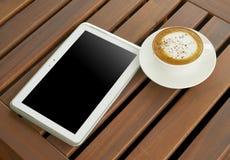 Copo branco do café do cappuccino com exposição do banco da tabuleta do tela táctil de 10 polegadas na tabela de madeira Imagem de Stock