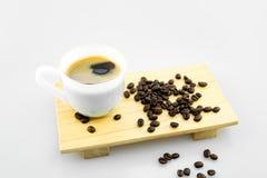 Copo branco do café quente com os feijões de café na placa de madeira e do fundo cinzento com espaço da cópia imagem de stock