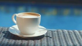 Copo branco do cappuccino na tabela de vime com fundo da água azul filme