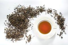 Copo branco do chá com forma da folha de chá secada no fundo branco Fotografia de Stock Royalty Free