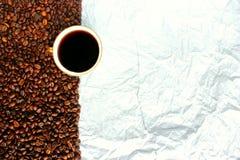 Copo branco dos feijões de café e o papel Foto de Stock