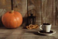 Copo branco enchido com os feijões de café em uma tabela de madeira imagens de stock